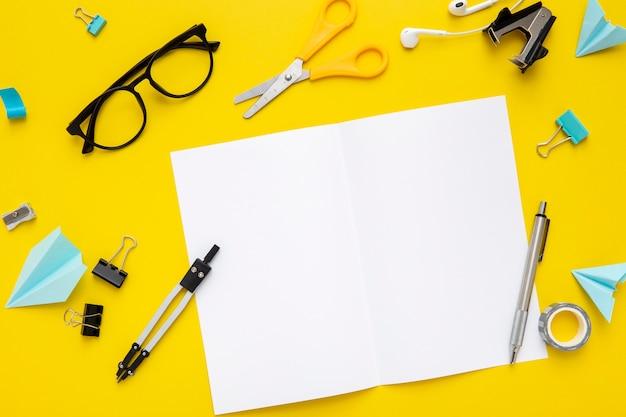 Variedade de artigos de papelaria vista superior em fundo amarelo