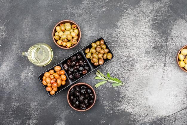 Variedade de azeitonas frias em um prato preto e tigelas de barro com um pote de azeite e folhas de oliveira vista superior no grunge cinza escuro