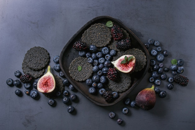 Variedade de bagas e figos com biscoitos pretos