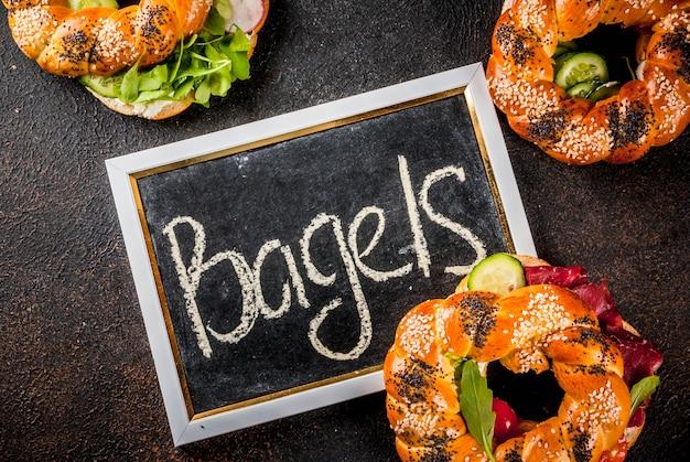 Variedade de bagels caseiros sanduíches com sementes de gergelim e papoula, queijo creme, presunto, rabanete, rúcula, rúcula, tomate cereja, pepino, fundo escuro de concreto acima