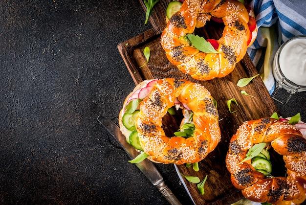 Variedade de bagels caseiros sanduíches com sementes de gergelim e papoula, queijo creme, presunto, rabanete, rúcula, rúcula, tomate cereja, pepino, na tábua. superfície de concreto escuro acima