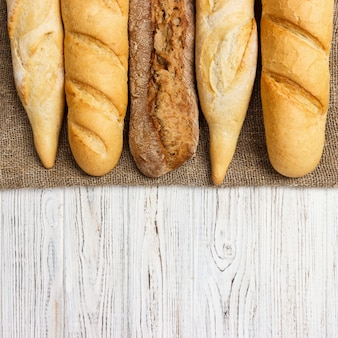 Variedade de baguetes francesas frescas sobre uma mesa de madeira