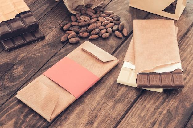 Variedade de barras de chocolate e grãos de cacau na mesa de madeira
