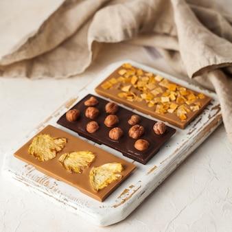 Variedade de barras de chocolate vegan, três tipos de chocolate com avelãs inteiras, abacaxi, fatias de manga ...