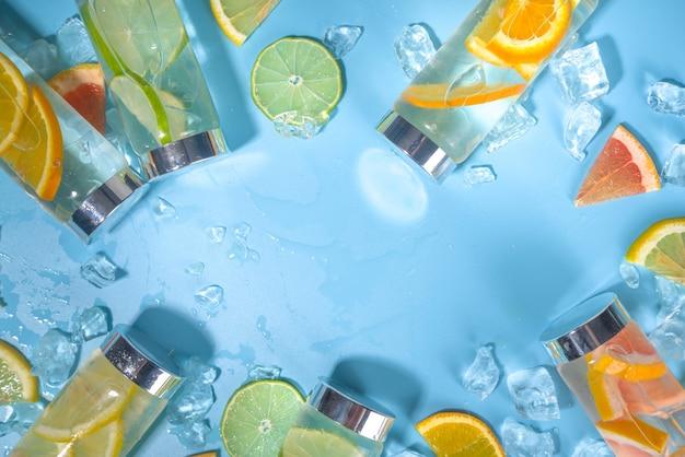 Variedade de bebidas geladas em garrafas, garrafas de água com infusão de verão, coquetéis saudáveis de limonada com diferentes frutas cítricas - limão, laranja, toranja, limão, espaço de cópia de fundo brilhante