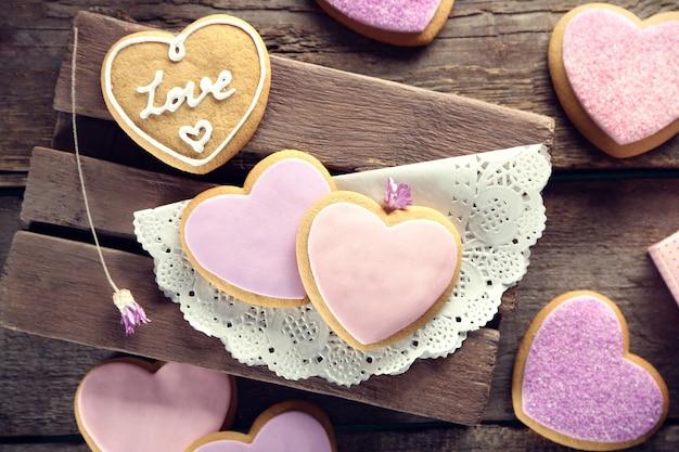 Variedade de biscoitos cor de rosa em superfície de madeira