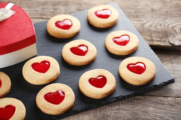 Variedade de biscoitos do amor com caixa de presente no suporte cinza