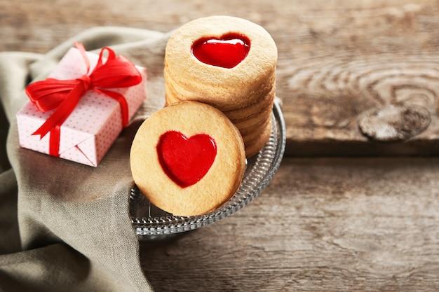 Variedade de biscoitos do amor com presente e pano na superfície de madeira, closeup