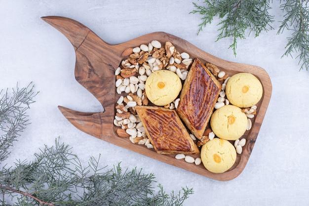 Variedade de biscoitos saborosos em uma placa de madeira com nozes