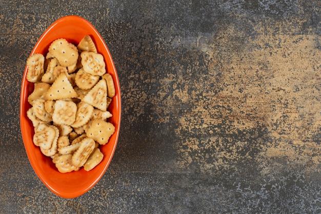 Variedade de biscoitos salgados em uma tigela de laranja.