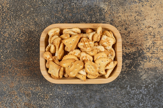 Variedade de biscoitos salgados em uma tigela de madeira.