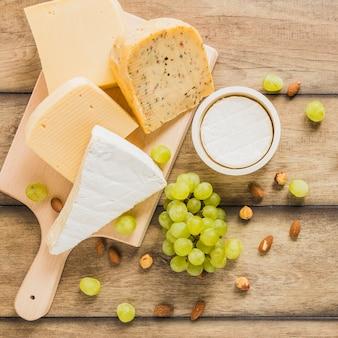 Variedade de blocos de queijo com uvas; amêndoas e castanhas na mesa de madeira