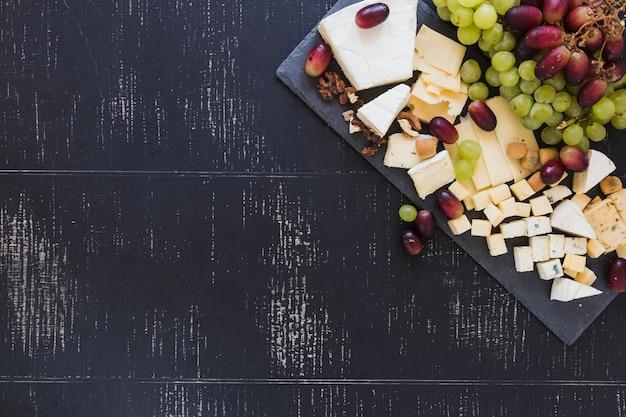 Variedade de blocos de queijo com uvas no pano de fundo texturizado preto