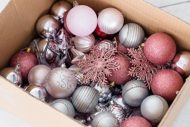 Variedade de bolas decorativas de natal em uma caixa. mistura de flocos de neve e brinquedos de enfeites de prata e ouro rosa