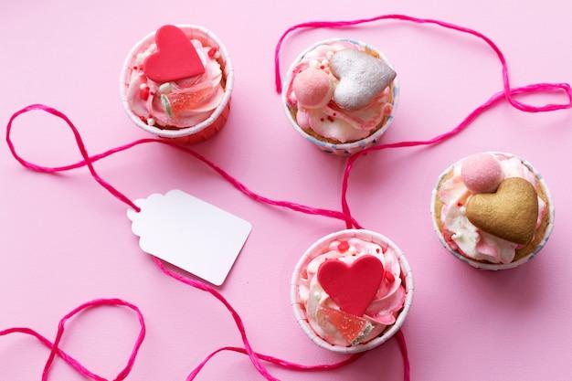 Variedade de bolos saborosos no fundo rosa.