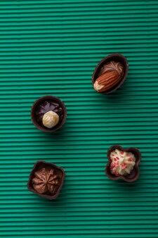 Variedade de bombons de bombons de bombons marrons sobre fundo verde. doces deliciosos doces de chocolate.