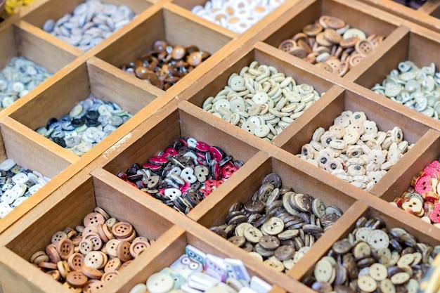 Variedade de botões de cerâmicas coloridas e miçangas para fazer acessórios artesanais.