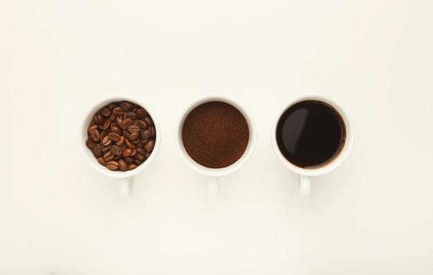 Variedade de café em xícaras. grãos inteiros, café moído e americano acabado de fazer, isolado no fundo branco, vista superior, copie o espaço