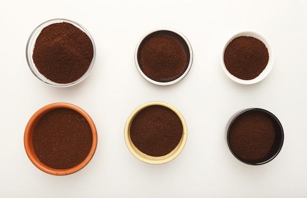 Variedade de café moído em várias taças, isoladas no fundo branco. sementes torradas, vista de cima, espaço de cópia