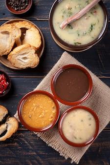 Variedade de caldos, feijão, mandioca e caldo verde. alimentos de inverno. vista do topo