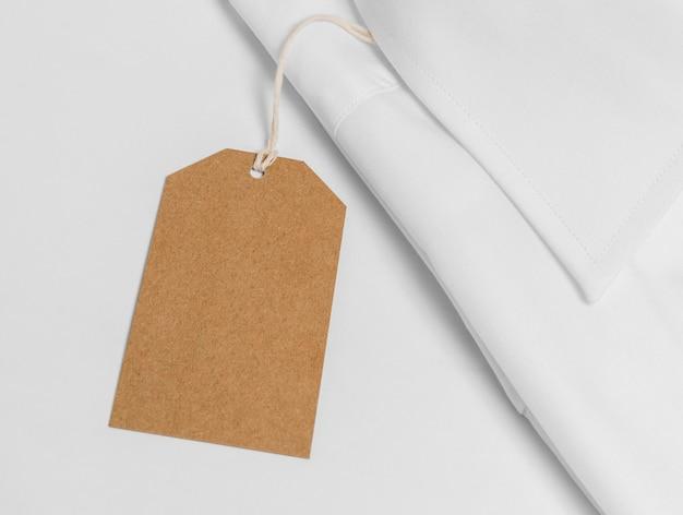 Variedade de camisa dobrada com close-up de etiqueta de papelão em branco