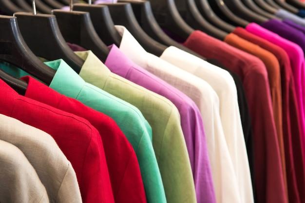 Variedade de camisa multicolorida pendurada na prateleira no mercado