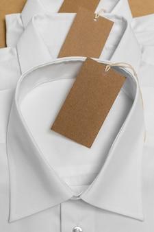 Variedade de camisas dobradas com etiqueta de papelão em branco