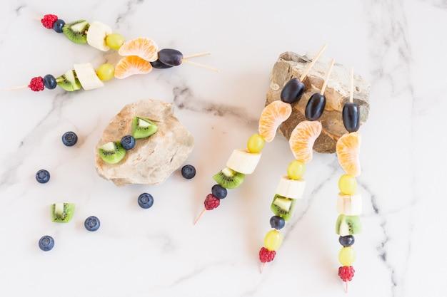 Variedade de canapés de frutas em pedras, fundo de mármore branco. vitaminas vegetais.