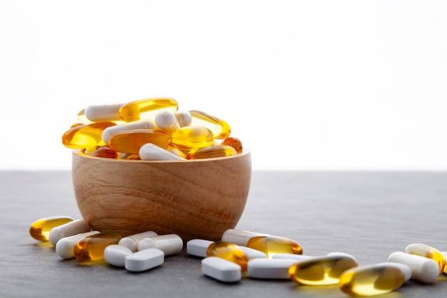 Variedade de cápsulas moles de medicina farmacêutica, pílulas na tigela de madeira no fundo cinza