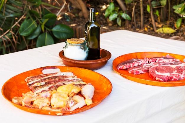 Variedade de carne crua na placa vermelha sobre a mesa