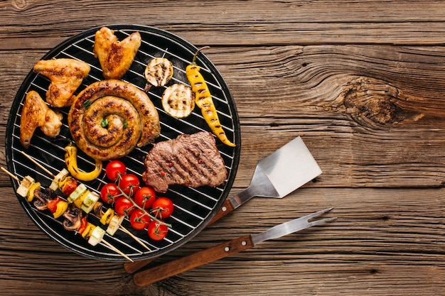 Variedade de carne marinada e salsichas grelhados na churrasqueira sobre fundo de madeira