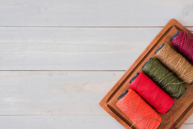 Variedade de carretéis coloridos brilhantes na bandeja de madeira sobre a mesa branca
