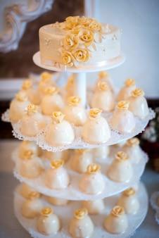 Variedade de carrinho de bolo com uma deliciosa sobremesa em uma mesa de casamento.