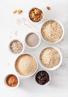 Variedade de cereais crus e nozes no café da manhã. flocos de aveia e corte de aço, cevada, nozes, chia, passas. ingredientes saudáveis