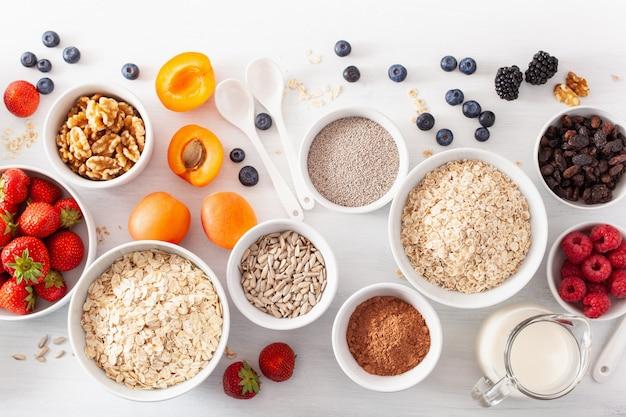 Variedade de cereais crus, frutas e nozes no café da manhã. flocos de aveia e corte de aço, cevada, nozes, chia, damasco, morango. ingredientes saudáveis