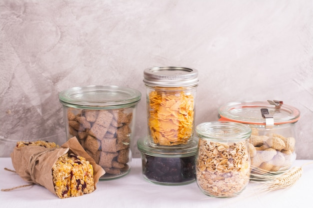 Variedade de cereais e nozes em frascos de armazenamento