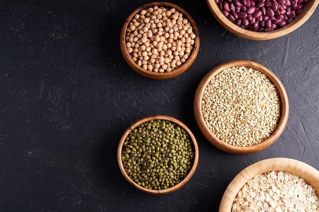 Variedade de cereais, leguminosas, cereais, grãos, lentilhas, grão de bico, ervilha, feijão, aveia em tigelas de madeira