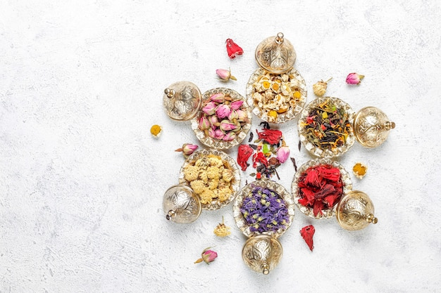 Variedade de chá seco em mini placas vintage douradas. tipos de chá