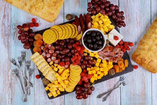 Variedade de charcutaria, queijo, azeitonas, frutas e presunto na mesa de madeira