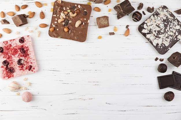 Variedade de chocolate delicioso no fundo branco de madeira