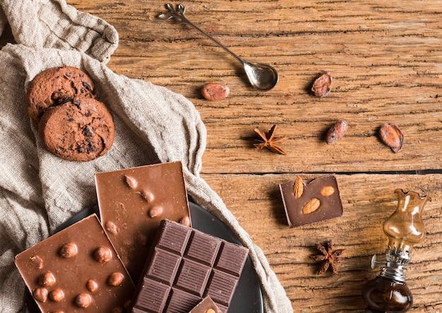 Variedade de chocolates de vista superior e biscoitos na mesa de madeira