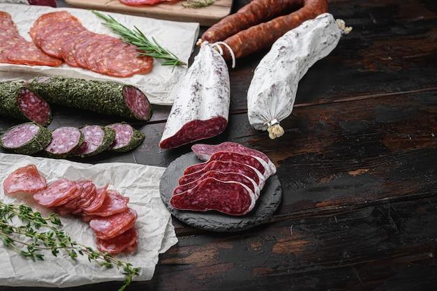 Variedade de chouriço curado a seco, fuet e outras salsichas cortadas em fatias com ervas na velha mesa de madeira.
