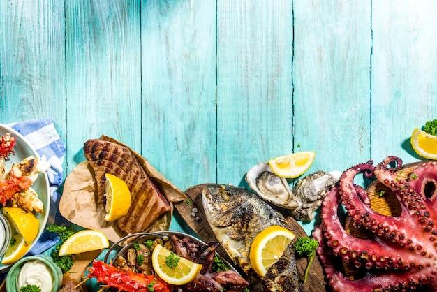 Variedade de churrasco com comida mediterrânea grelhada - peixe, polvo, camarão, caranguejo, frutos do mar, mexilhões, festa de churrasco de dieta de verão, com kebab, molhos, fundo de madeira azul claro