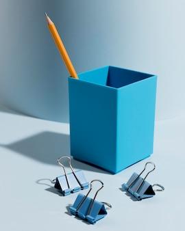 Variedade de close-up de clipes de papel e lápis na mesa