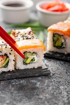 Variedade de close-up de rolos de sushi maki com pauzinhos na ardósia