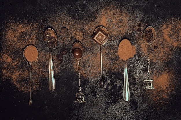 Variedade de colheres de prata com cacau em pó