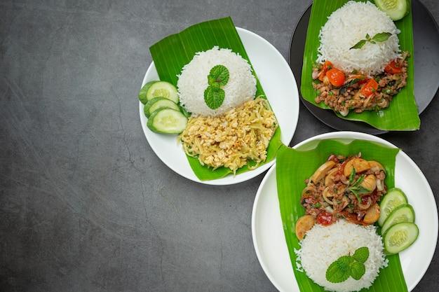 Variedade de comida tailandesa colocada em folha de bananeira