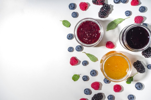 Variedade de compotas de frutas e bagas sazonais de verão em pequenos potes, conceito de conservas caseiras, marmeladas ou confitures com frutas frescas no espaço de cópia de fundo branco
