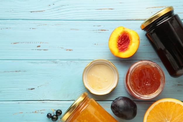 Variedade de compotas, frutas frescas sazonais e frutas sobre fundo azul com espaço de cópia.