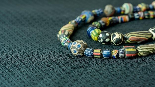 Variedade de contas de vidro antigas em colares sobre fundo preto de seda tailandesa